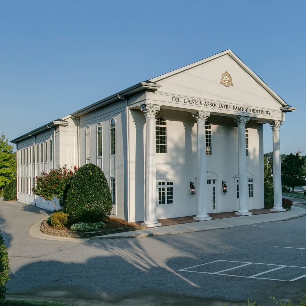 Big white dentist office with columns in Angier NC during Spring