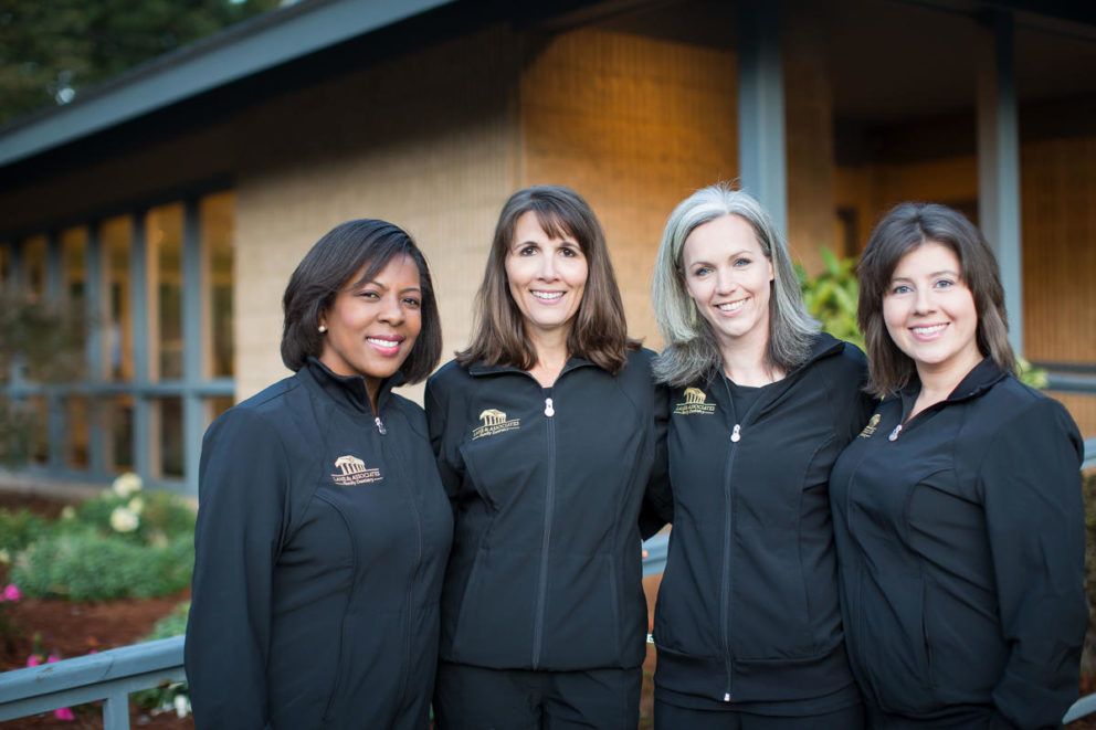 Group of four Lane & Associates Employees with arms around each other in black scrubs