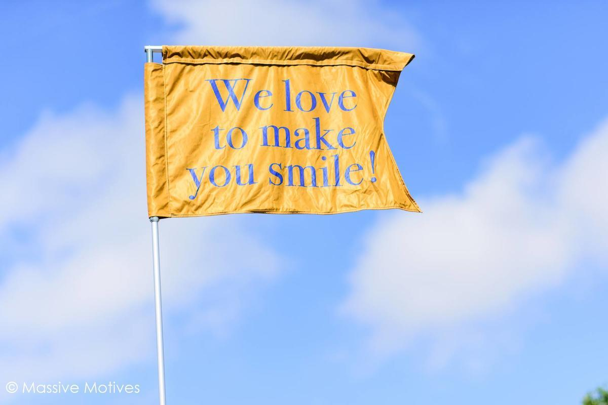 We love to make you smile motto gold flag in the blue sky