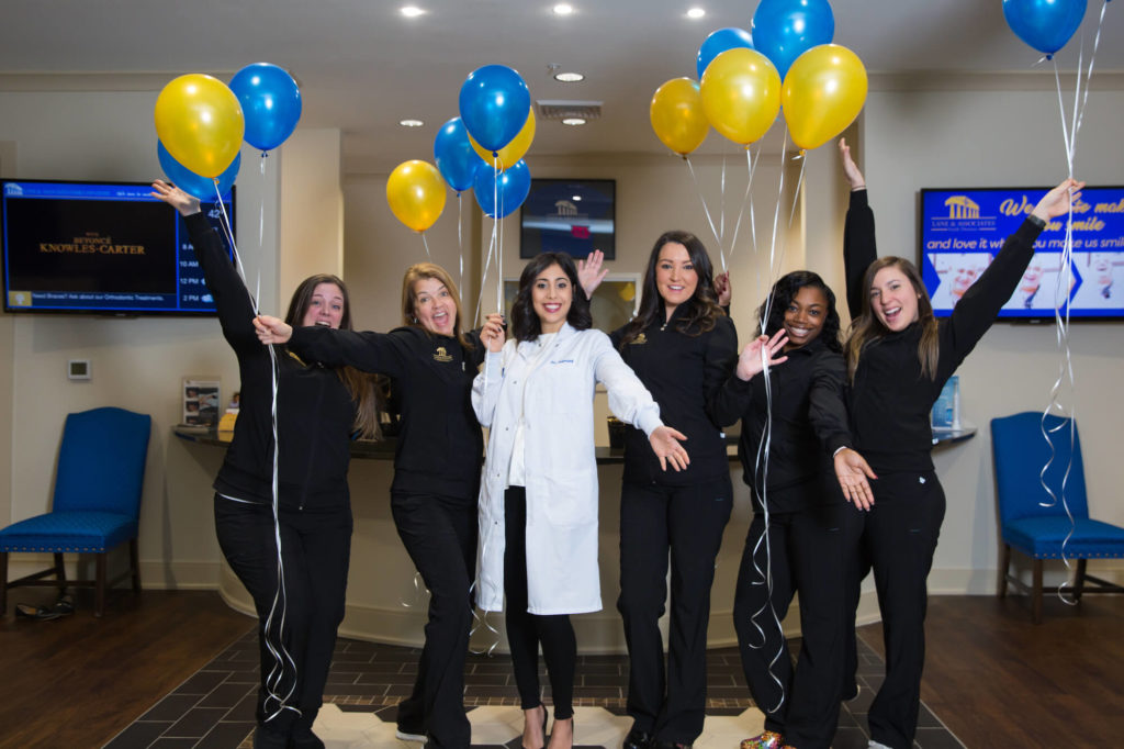 Group of dentists and dental assistants holding blue and gold balloons smiling and laughing