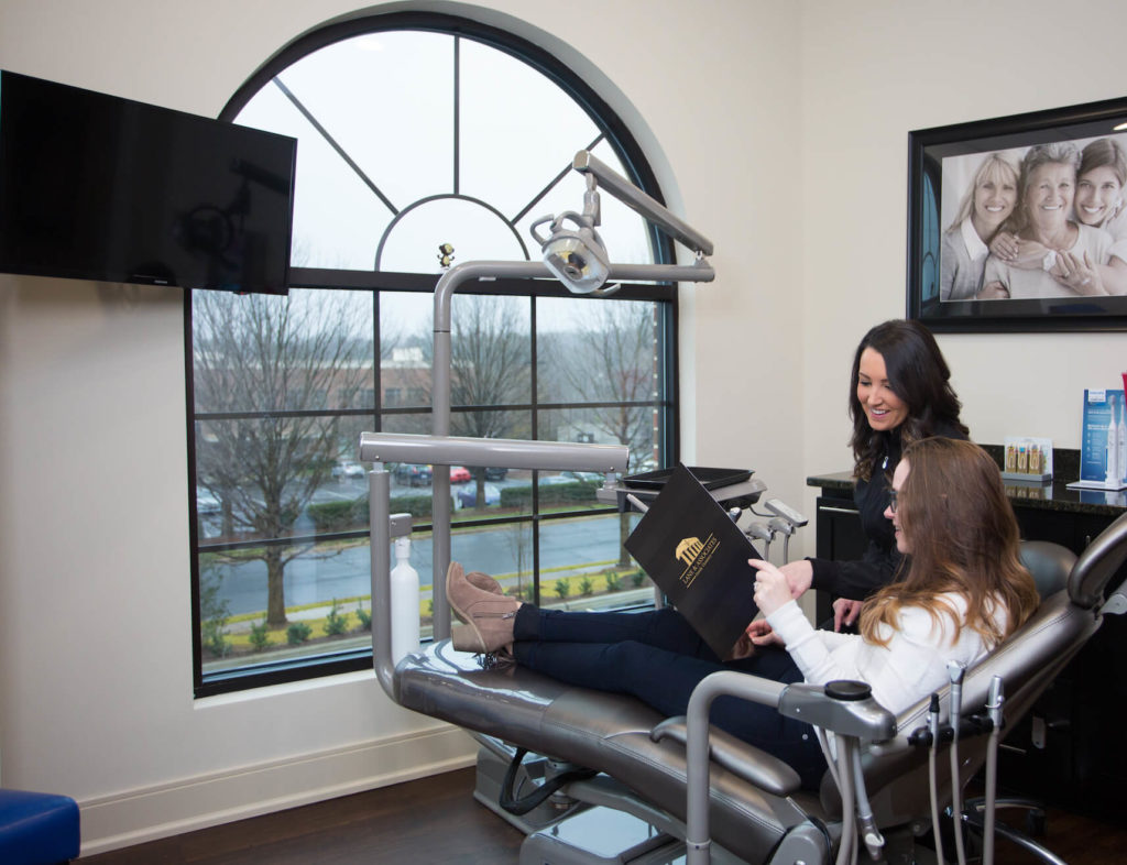 Patient in dental chair holding folder talking to assistant about dental treatment