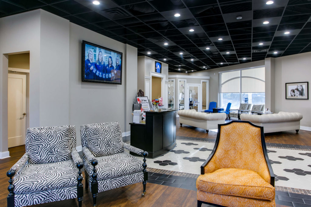 Lobby area of Lane and Associates Cary Tryon with black ceilings and bright lights orange chairs zebra striped chairs and concierge desk
