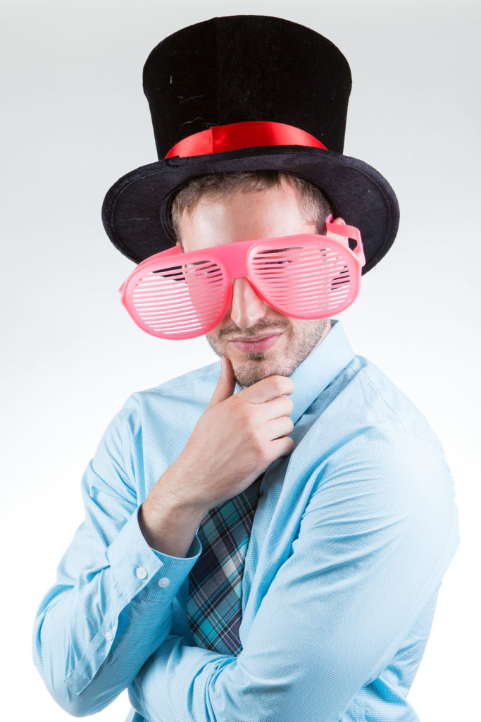 Dr. Zachary Neitzey wearing a large top hat and funny pink glasses