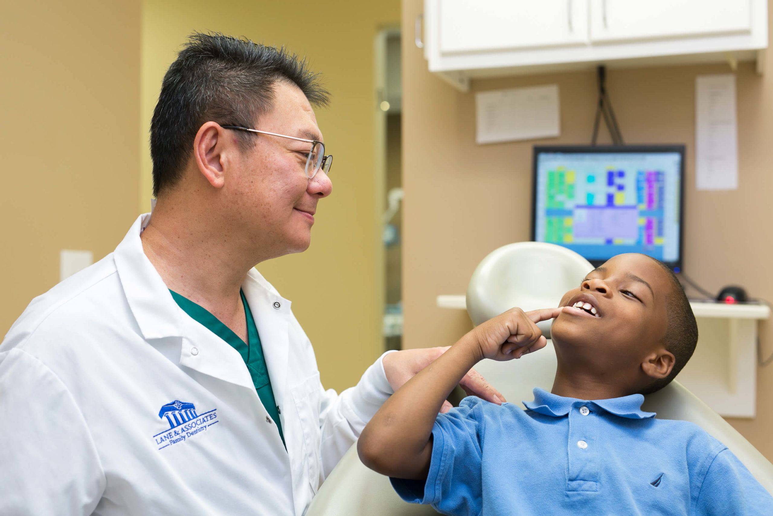 Boy showing dentist his tooth in dental chair