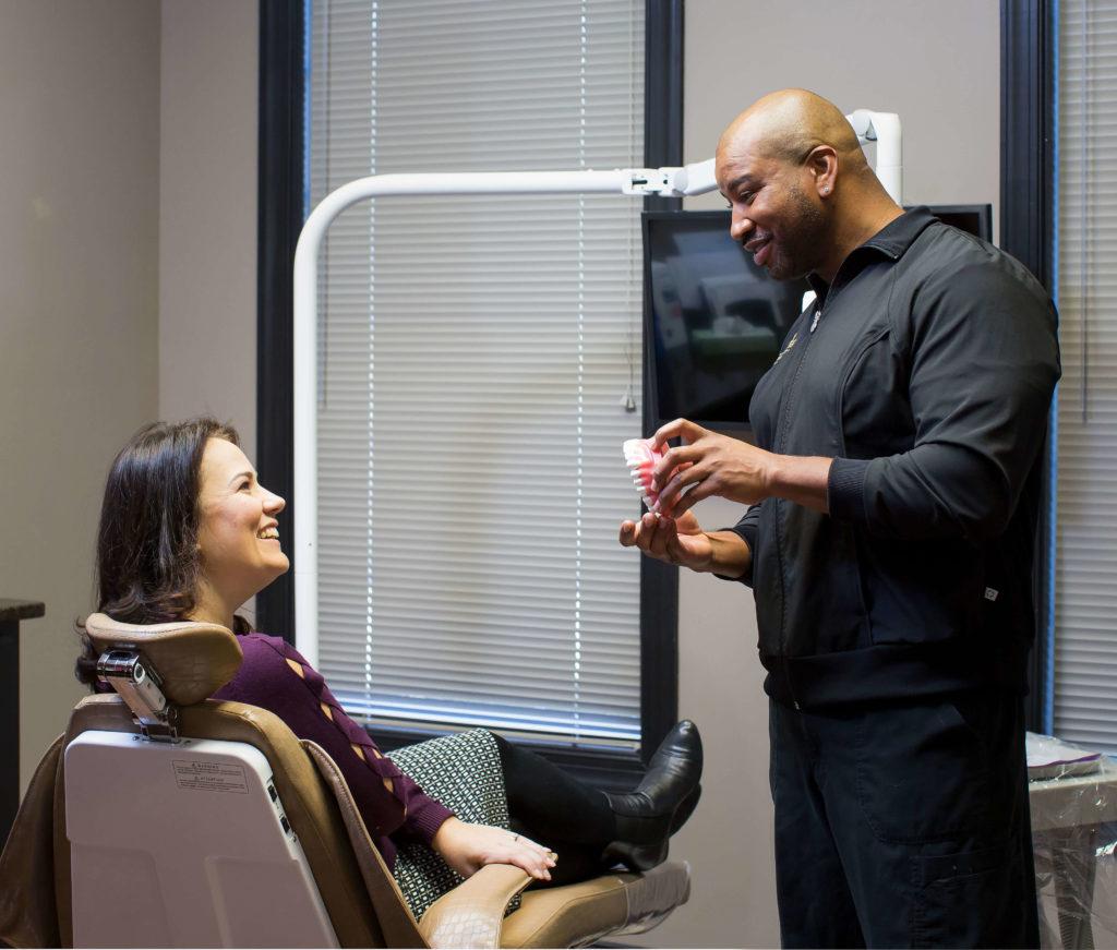 dental hygienist explains to patient