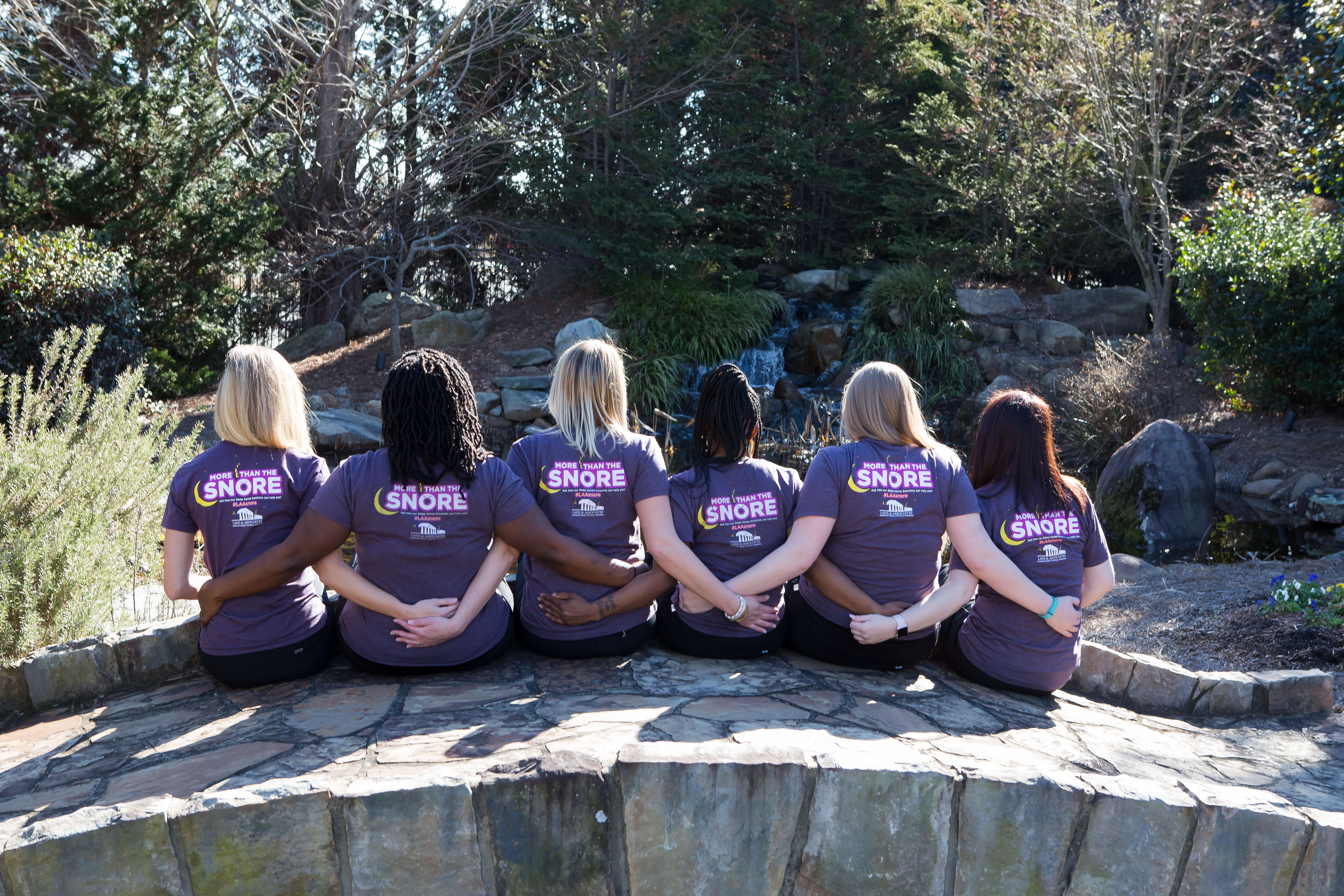 group of women sitting on a bridge in Garner NC wearing More Than the Snore purple t-shirts backs toward camera