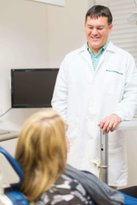 Raleigh Neuse doctor talking to patient in chair about cosmetic dentistry services in Raleigh NC