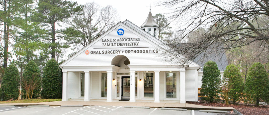 White building with triangular roof and columns and Lane DDS sign on front
