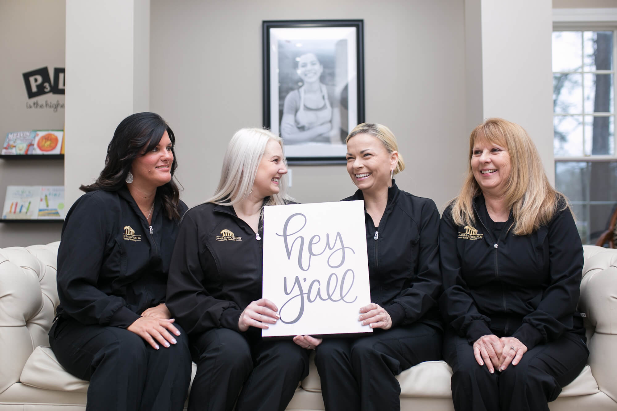 """Southern Pines Dental staff holding sign that says """"Hey y'all"""" laughing"""