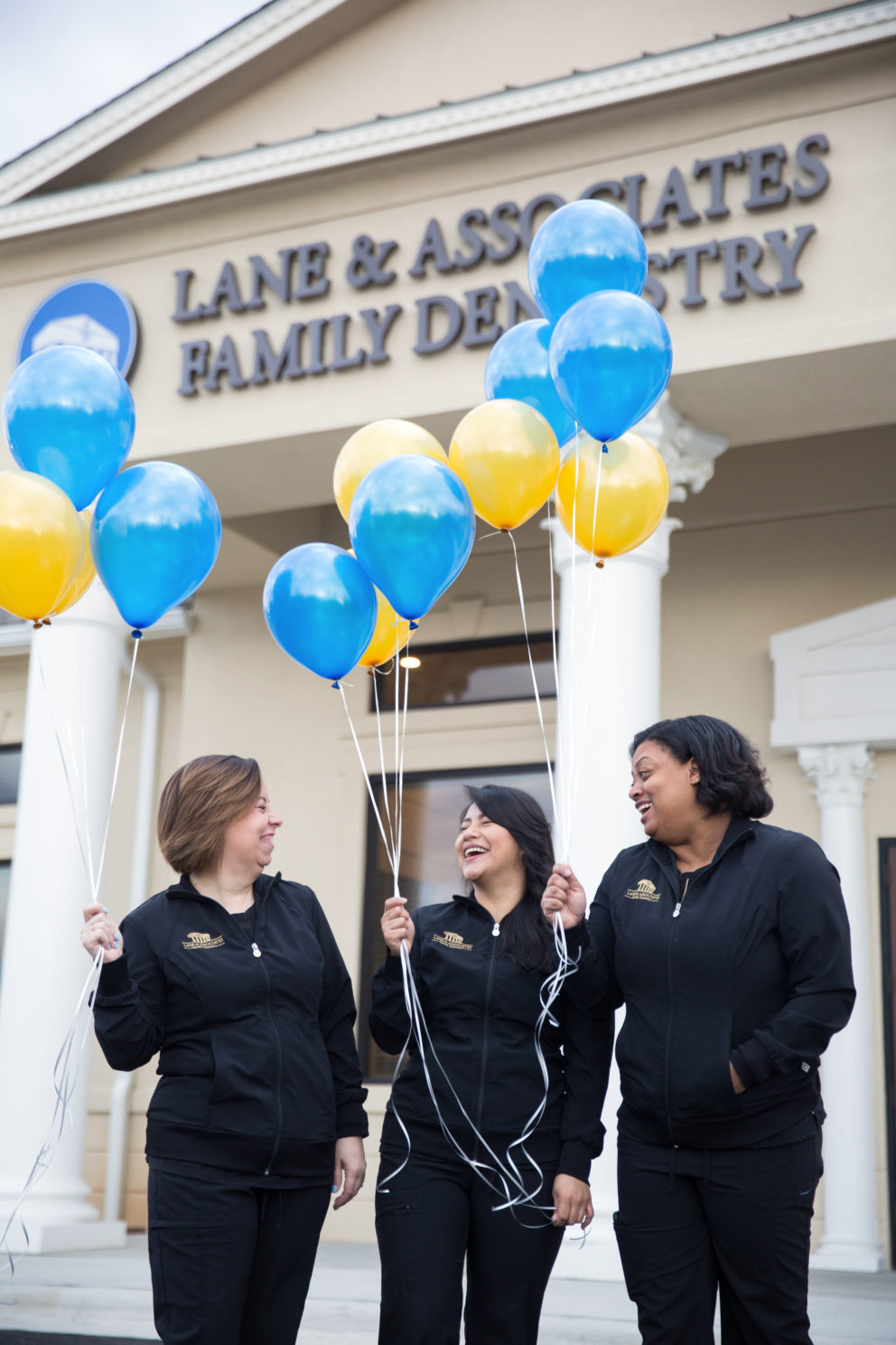 Group of Dental Assistants laughing with yellow and blue balloons in front of dental office in Winston Salem