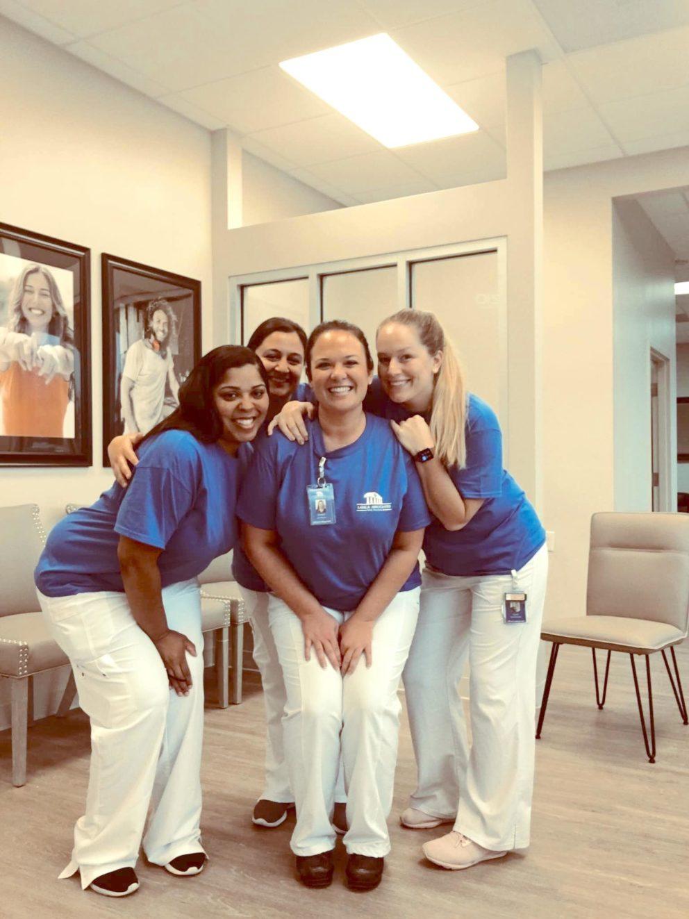 Mebane dentist office staff smiling for group shot in lobby