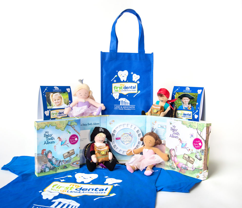 Cobalt blue bag with My First Dental Visit logo, two tooth fairy dolls, two pirate dolls, a kids sized t-shirt, and baby tooth album