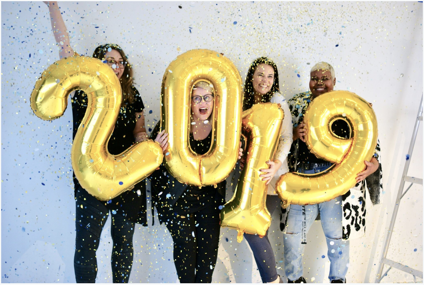 Gold 2019 number balloons being held by 4 people with confetti falling