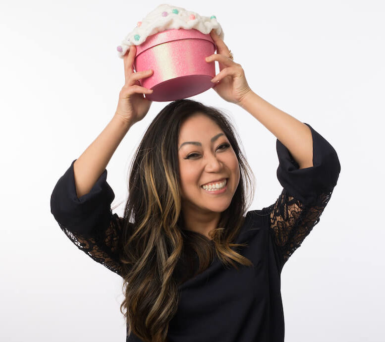 Dr. Angela Kang holding a pink cupcake shaped box over her head smiling big