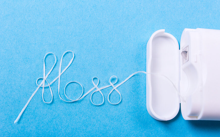 """Floss string spelling out """"Floss"""" with blue surface"""