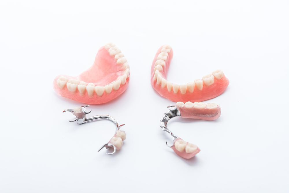 dentures and partials laid on white surface