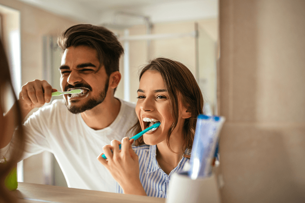 couple brushing their teeth at same sink