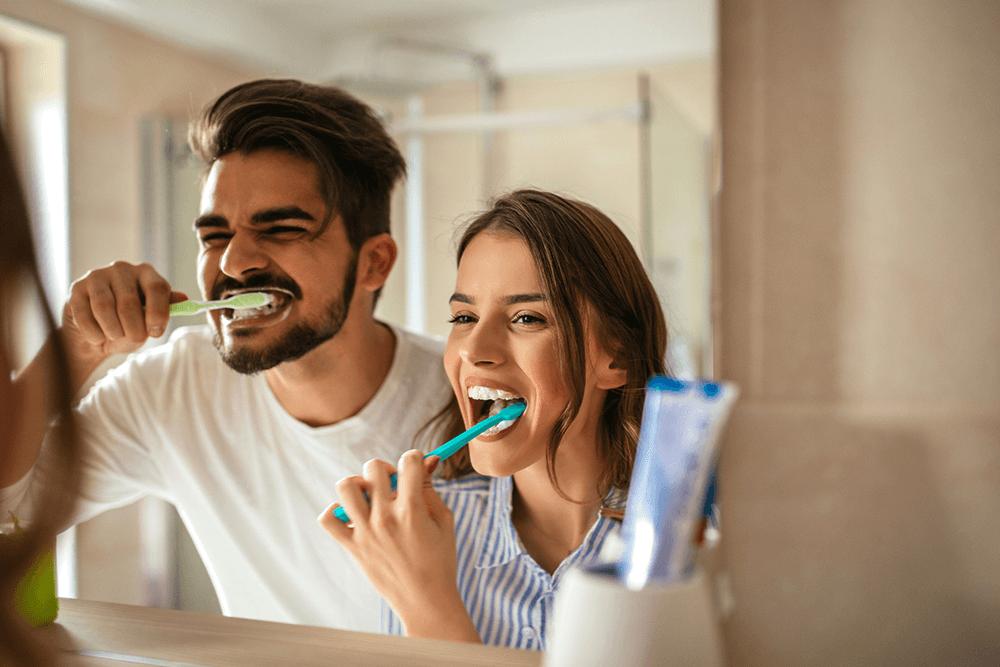 couple brushing their teeth at same sink