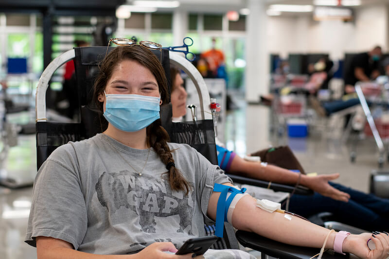 Girl with mask on giving blood