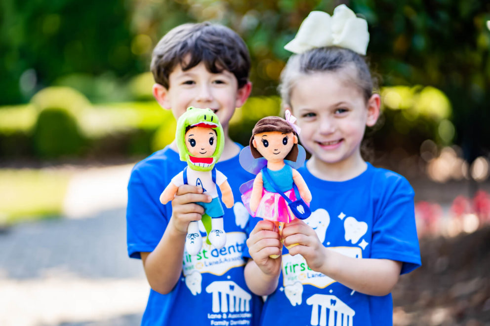Two children holding First Dental Visit dolls
