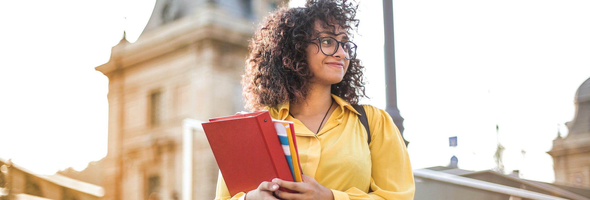 female carrying books wearing glasses